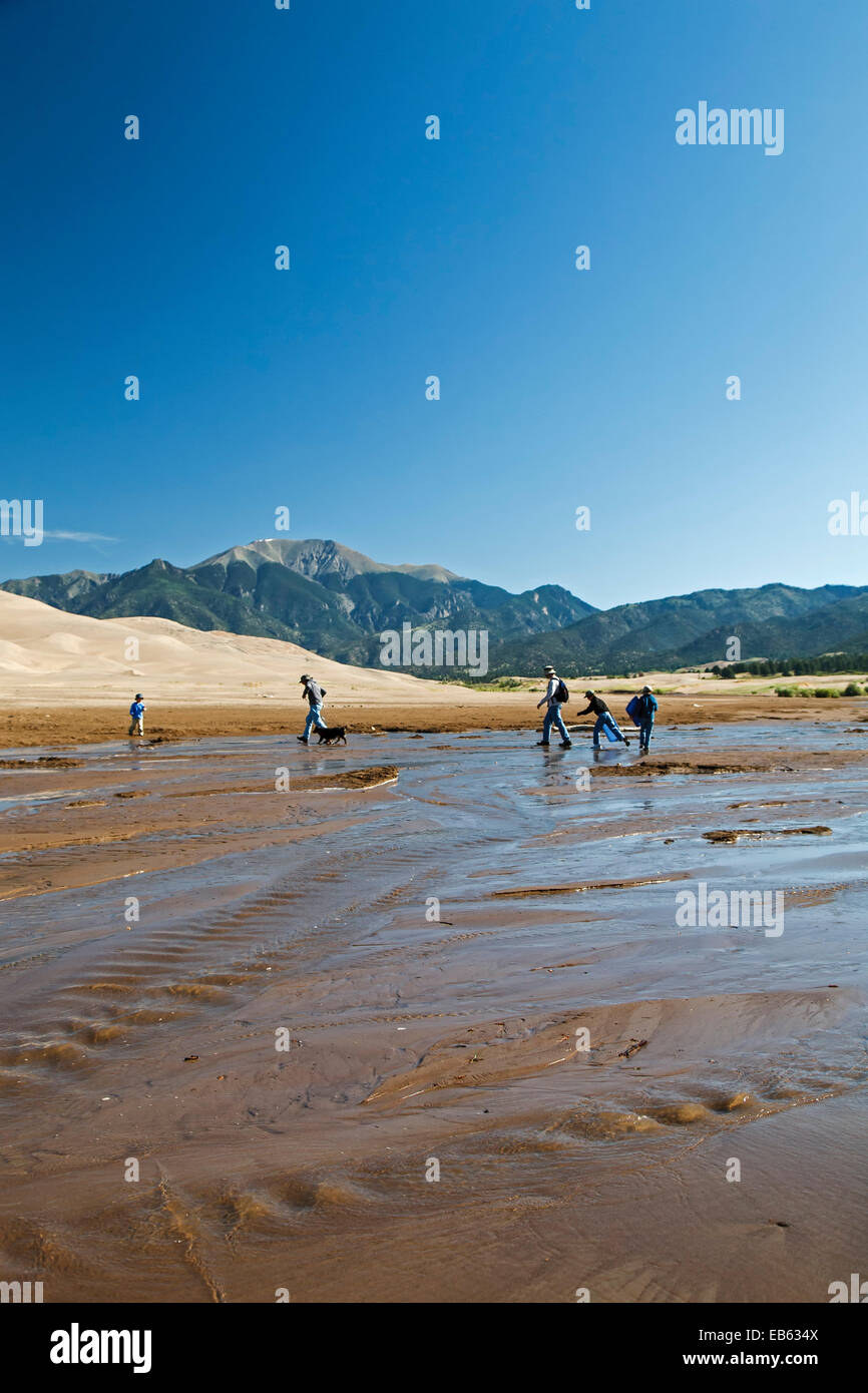 Family crossing Medano Creek, dunes and Sangre de Cristo Mountains, Great Sand Dunes National Park and Preserve, - Stock Image