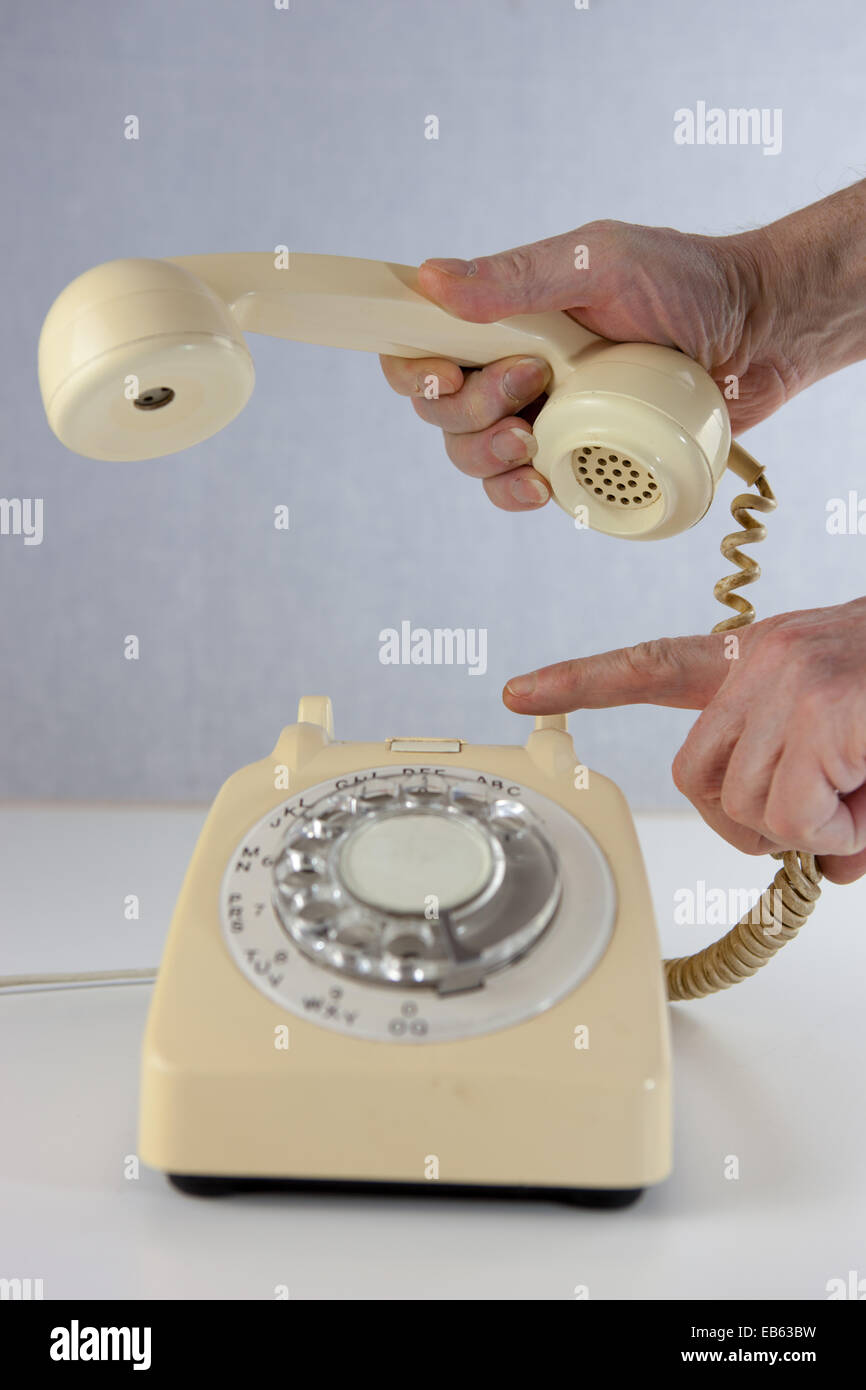 Hanging up a call on an old fashioned telephone. - Stock Image