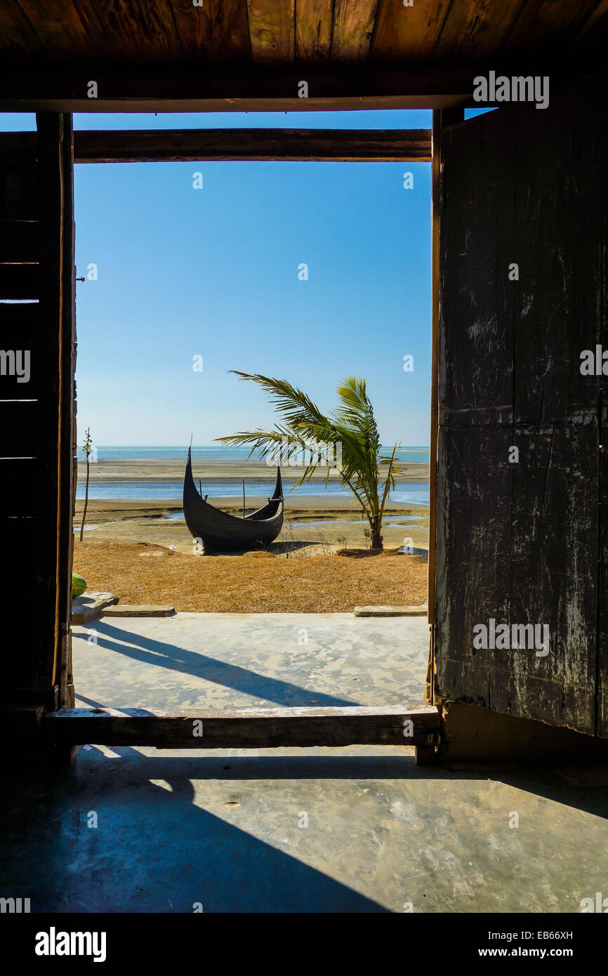Looking outside the door into a beach with a fishing boat and a coconut palm tree, in Cox's Bazar, Bangladesh - Stock Image