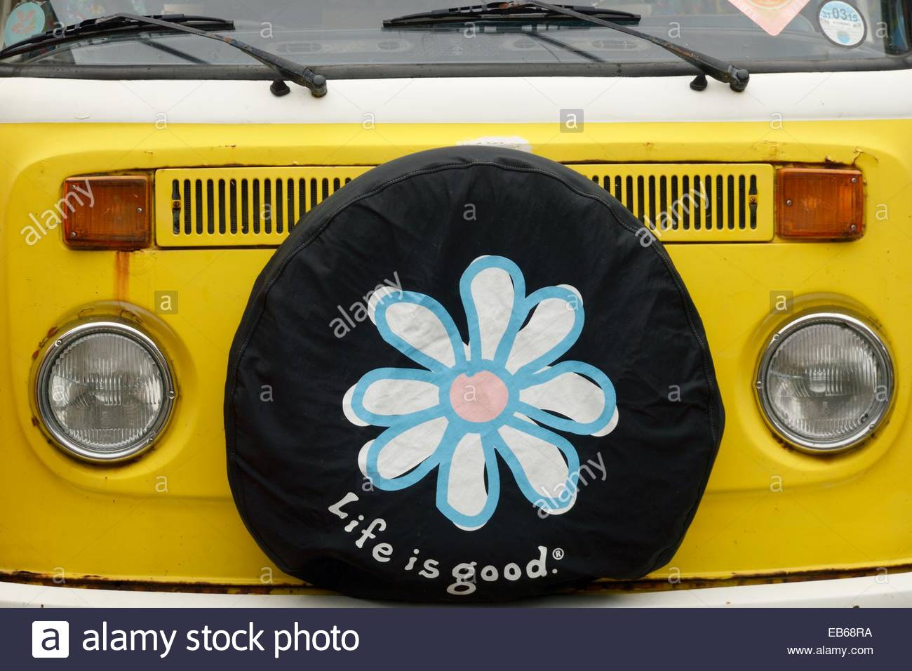Old yellow Volkswagen (VW) camper van with a 'Life Is Good' spare wheel cover. Stock Photo