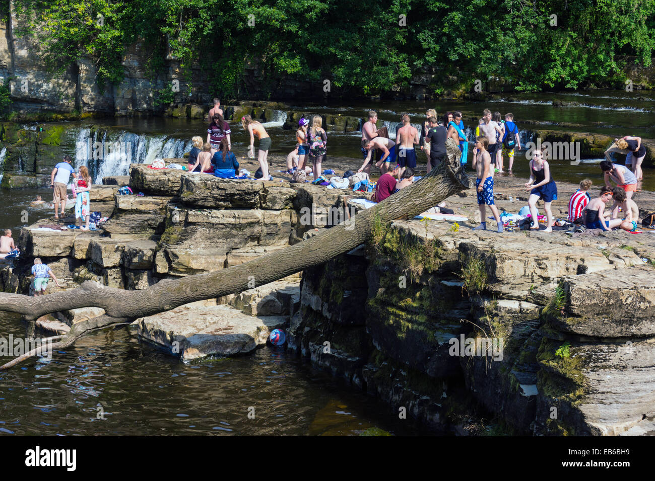 Crowds of young people playing in water, summer on the River Swale, Richmond, North Yorkshire, England Stock Photo