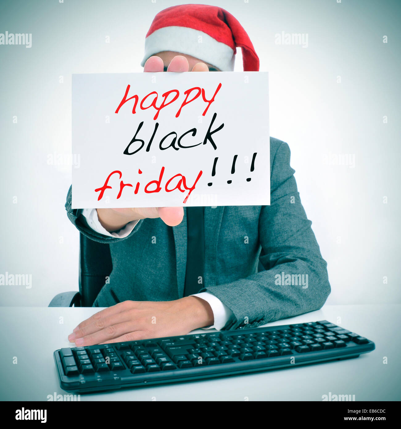a man with a santa hat in an office desk showing a signboard with the text happy black friday written in it - Stock Image