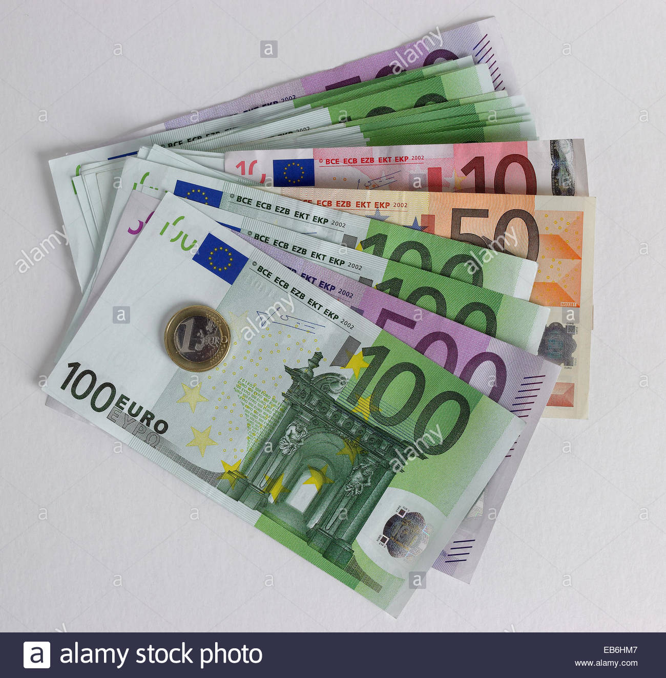 Overhead view of fan of mixed Euro notes with one Euro coin - Stock Image