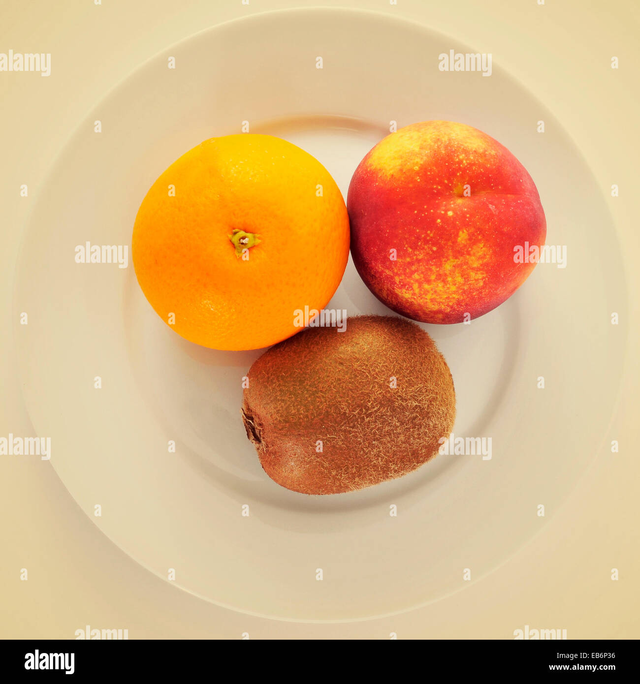 picture of a plate with an orange, a kiwi and a nectarine on a beige background, with a retro effect - Stock Image