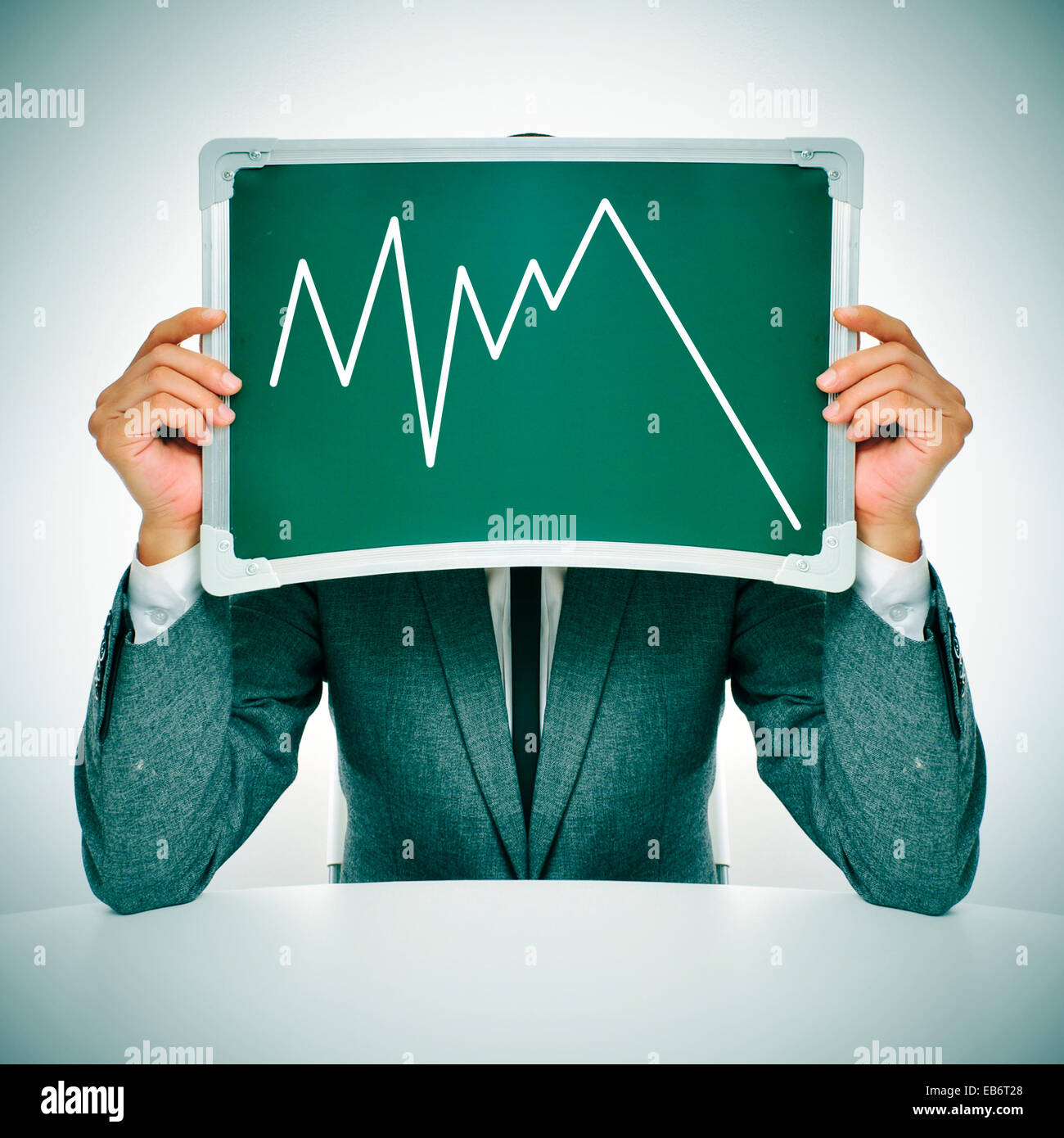 man wearing a suit sitting in a table showing a graph of economic losses - Stock Image