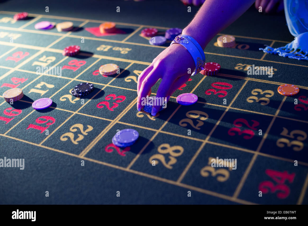 People laying placing bets playing at roulette gambling in a 'casino' at a wedding reception, UK - Stock Image