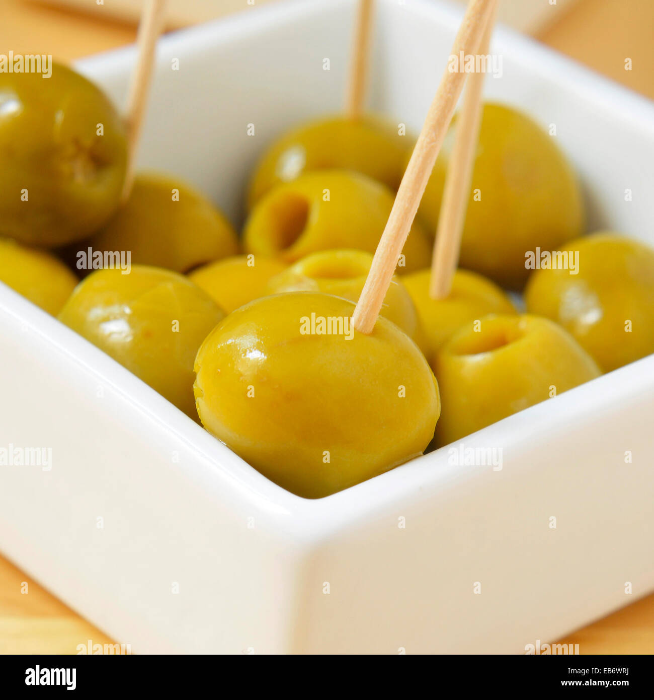 a bowl with olives with toothpicks served as tapas - Stock Image