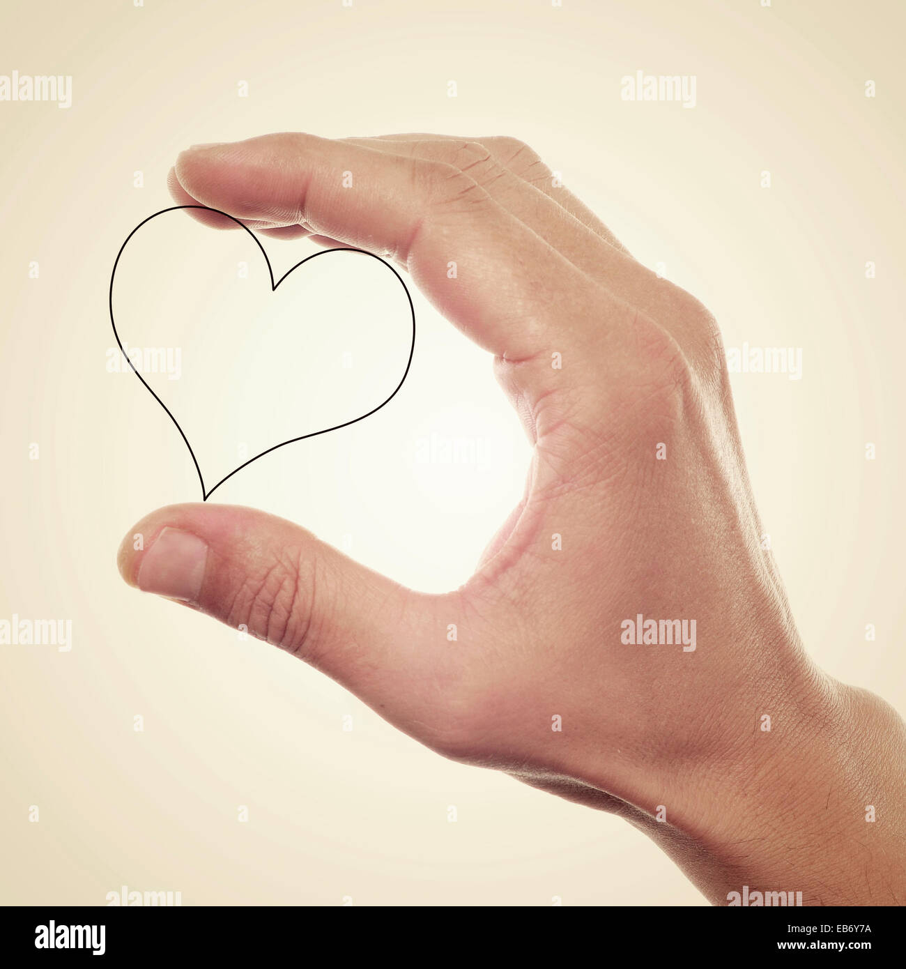picture of someone holding a drawn heart in his hand, with a retro effect - Stock Image