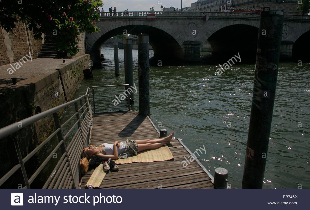 Woman sunbathing on the bank of Seine river, Paris. - Stock Image