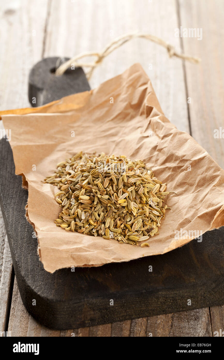 Heap of dried organic fennel seeds on wooden board on kitchen table - Stock Image