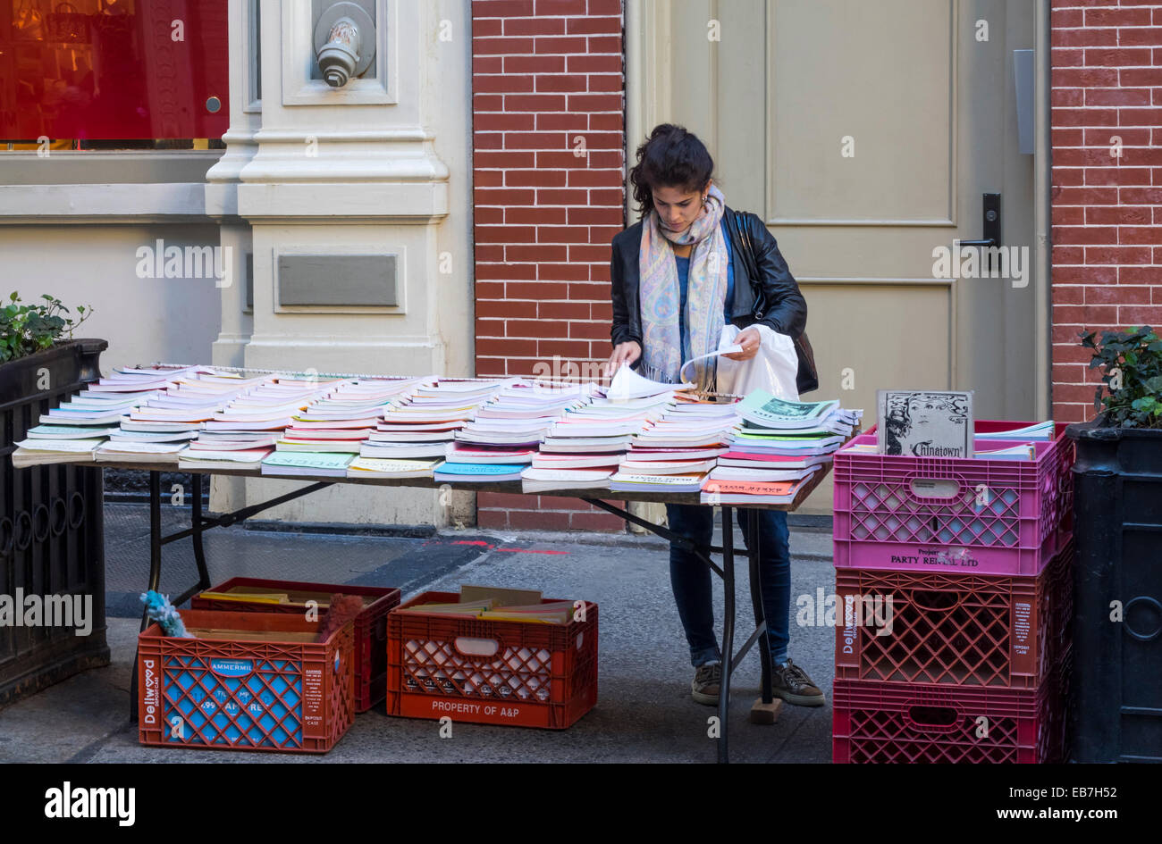 Young woman looking through printed copies of film scripts for sale at a street stall on Price Street n SoHo in - Stock Image