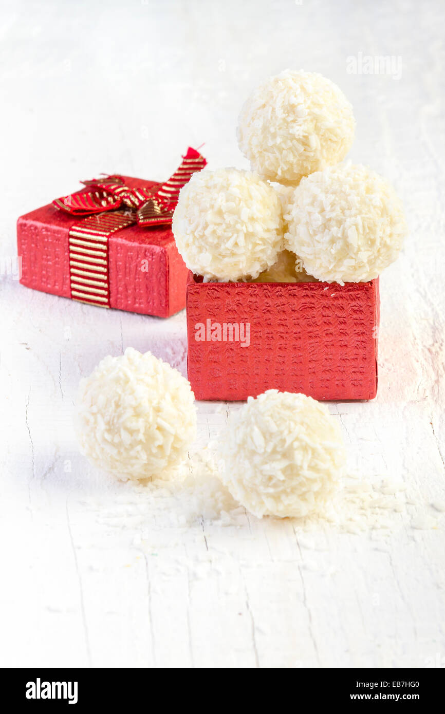 Coconut snowball truffles in the gift box on white background. Arrangement of coconut cookies on wooden elegant - Stock Image