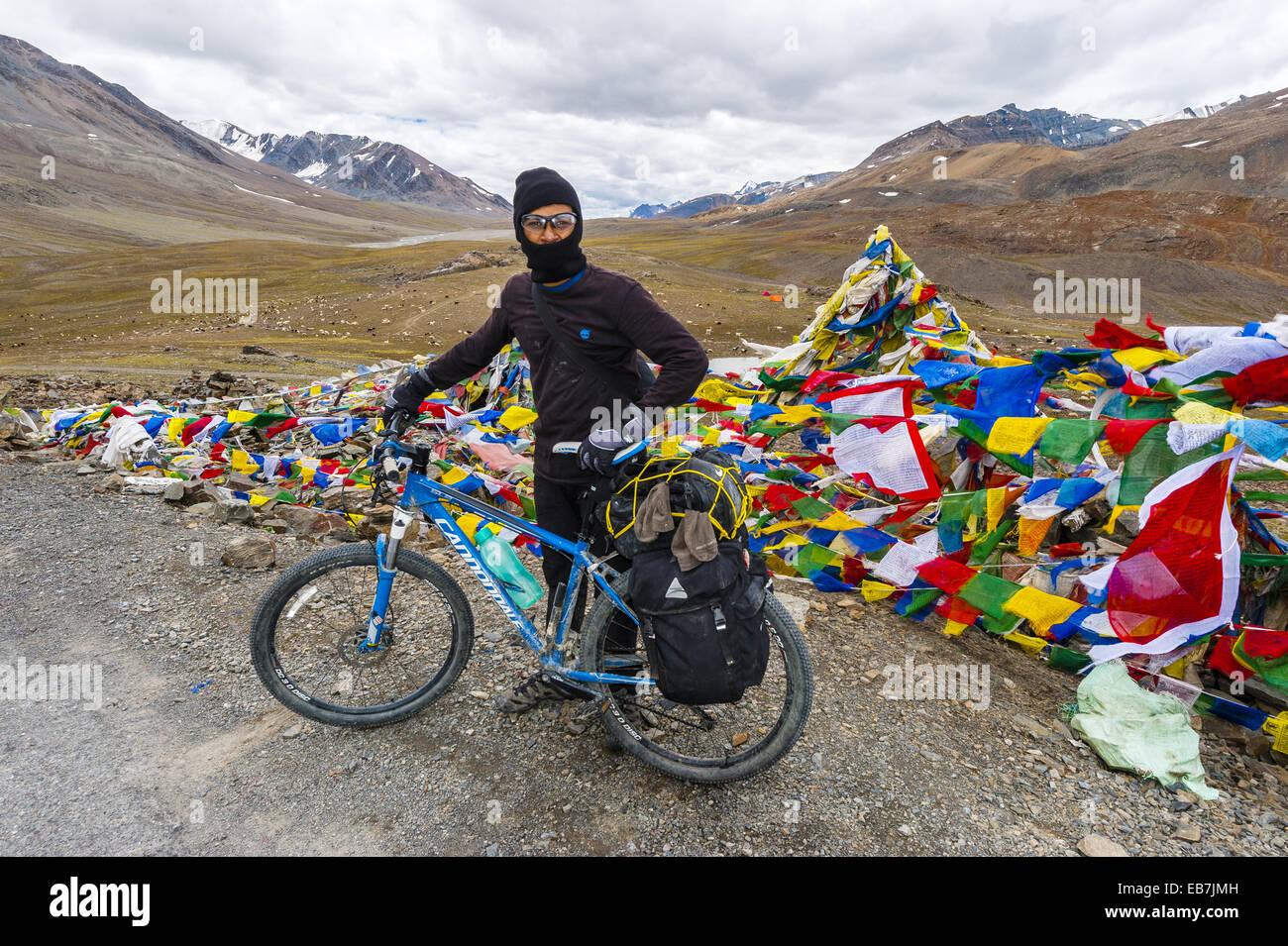 A bicyclist stops at the summit of 16,000 foot Bara-lacha Pass, Leh-Manali Highway, Himachal Pradesh, India. - Stock Image