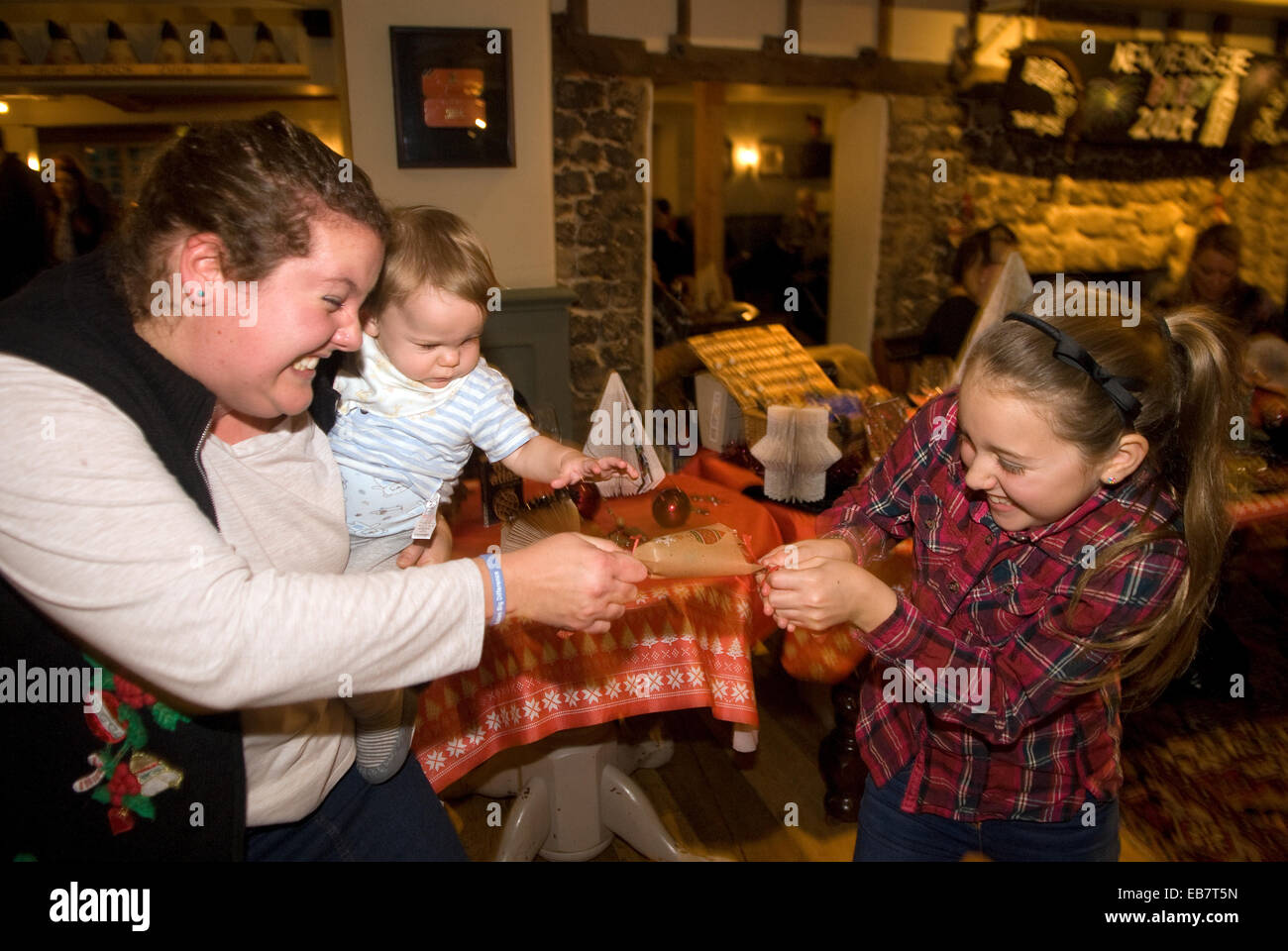 Pulling a christmas cracker in the pub, Liphook, Hampshire, UK. - Stock Image