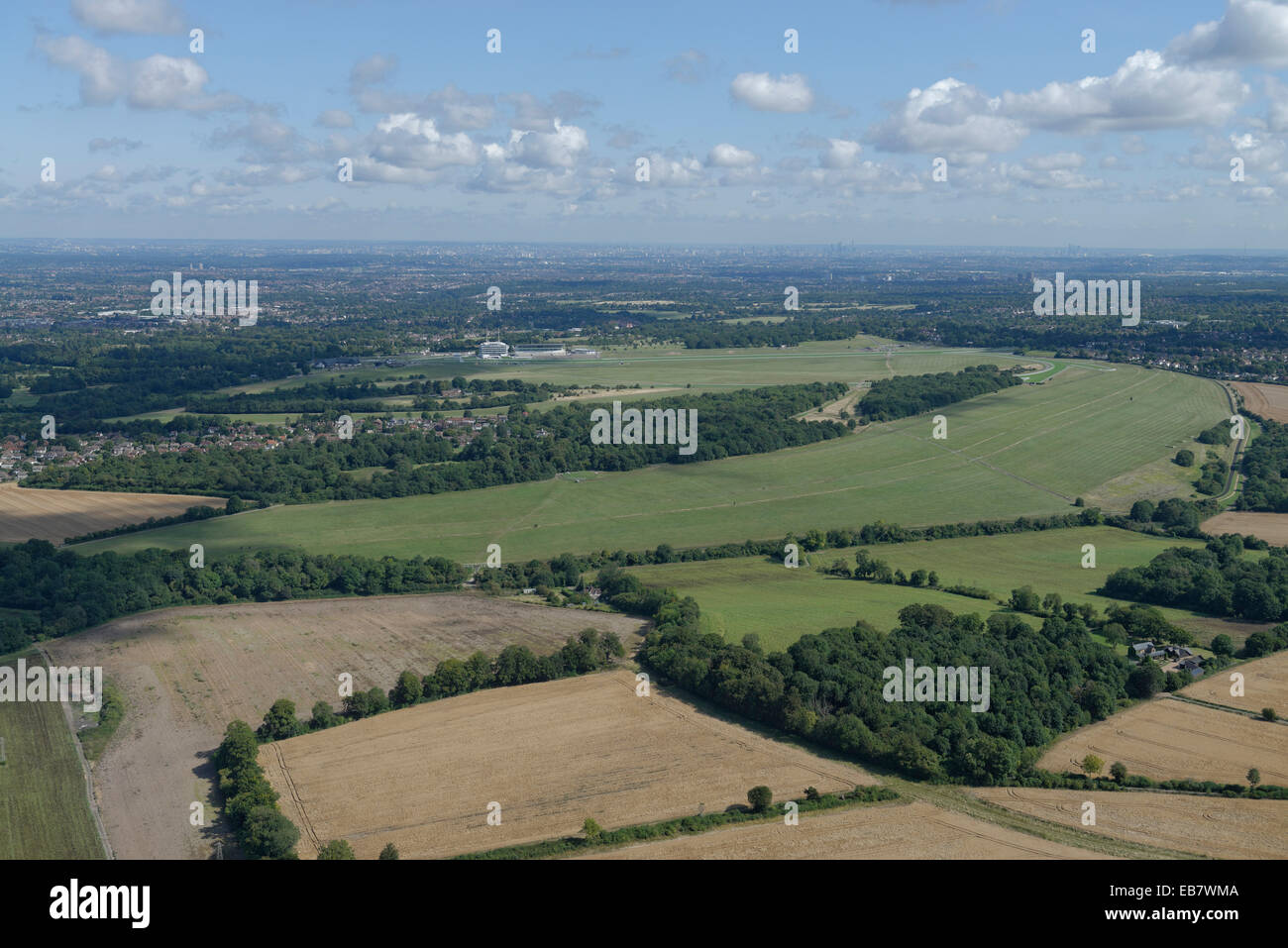 An aerial view of the Epsom Downs with the racecourse visible and the tall buildings of London in the distance Stock Photo