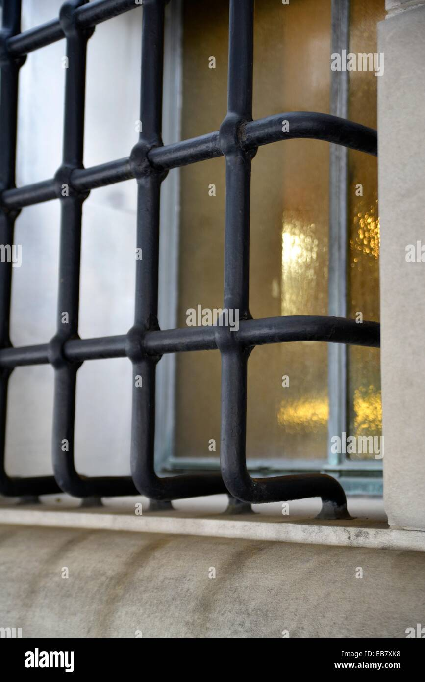 Wrought Iron Bars Covering an Amber Tinted Casement Window. - Stock Image