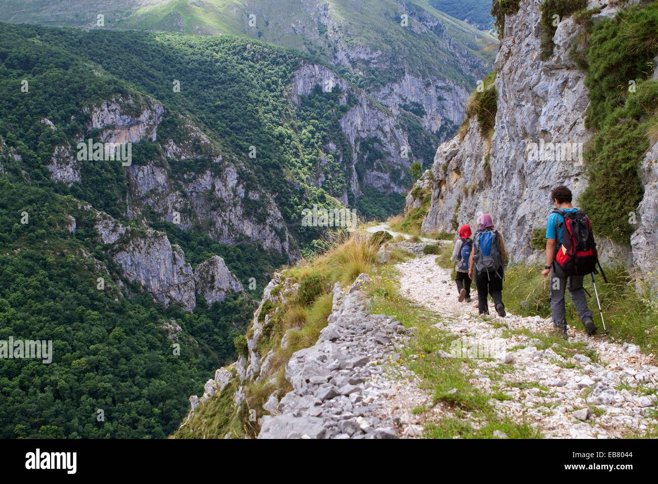 Hikers walking down from Tresviso a small village in Picos de Europa National Park by historic Urdón path to - Stock Image