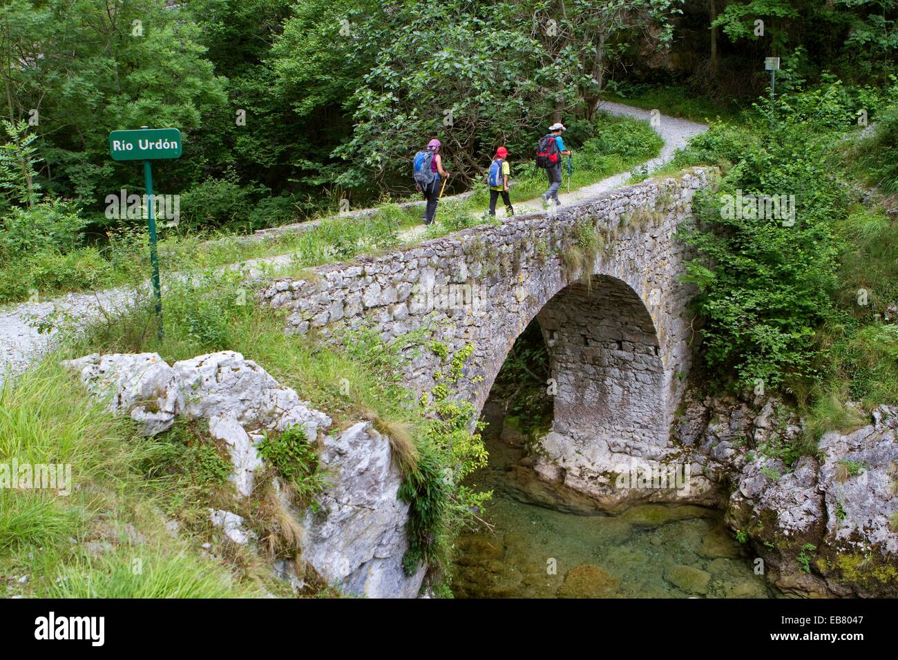 Hikers walking down from Tresviso small village in Picos de Europa National Park by historic Urdón path to - Stock Image