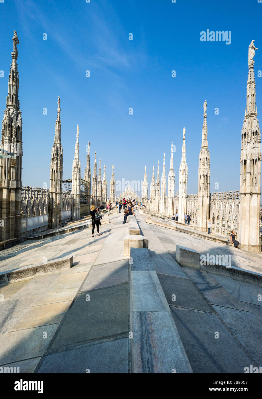 Italy, Milan, people between the spires and marle works of the Duomo cathedral rooftop - Stock Image