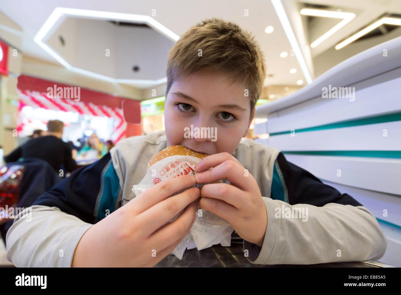 Teen boy eats  hamburger n Cafe - Stock Image