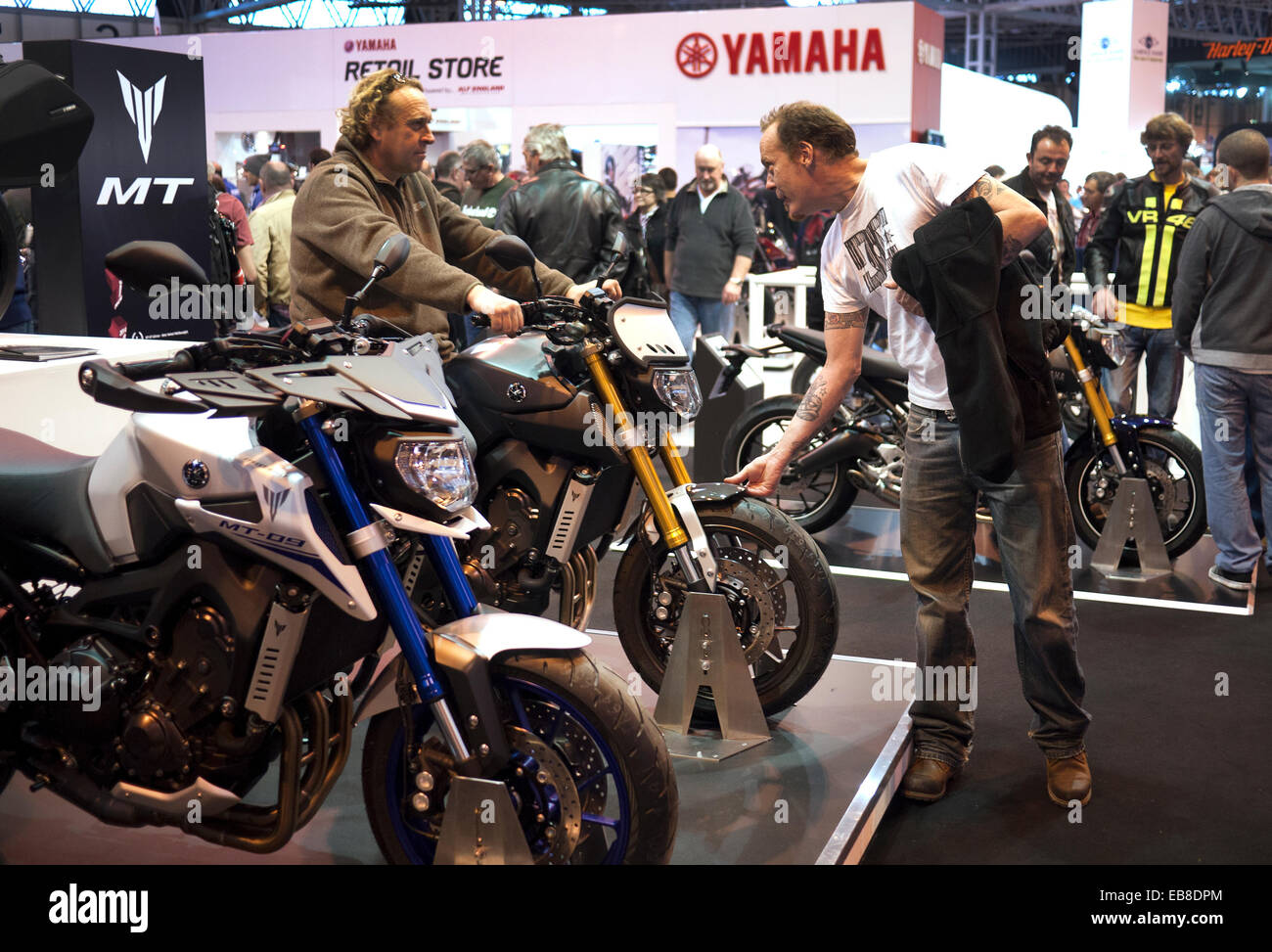 Visitors to the Motorcycle Live show at Birmingham's NEC, take a look at motorcycles on the Yamaha stand. - Stock Image