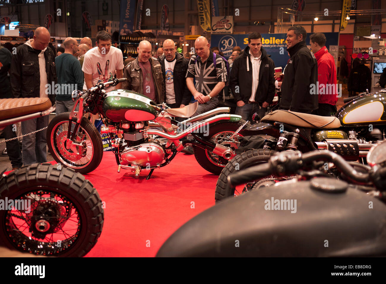 Visitors to the Motorcycle Live show at Birmingham's NEC, take a look at an custom Triumph motorcycle. - Stock Image