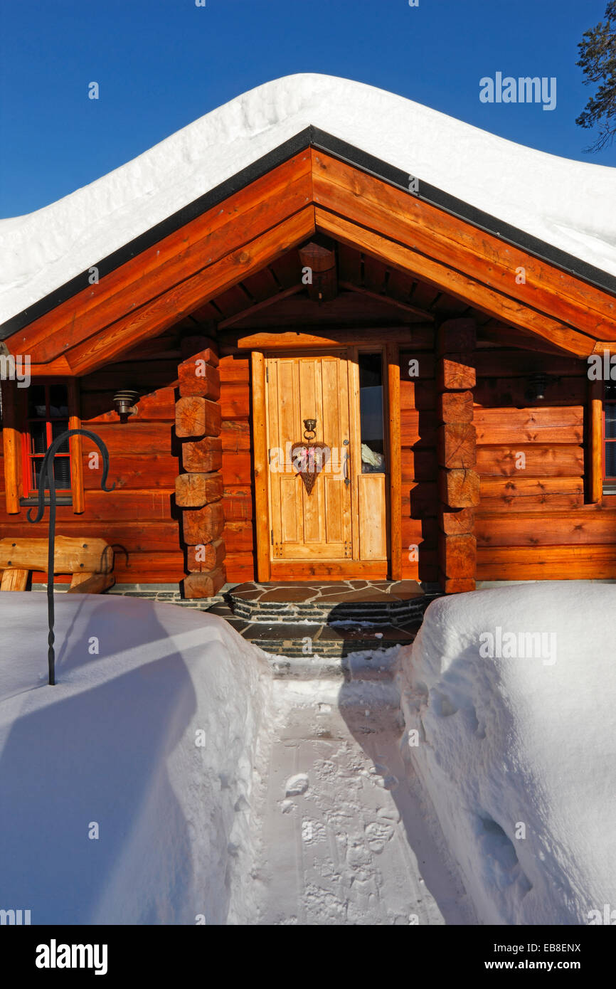Wooden house snow covered in winter Stock Photo