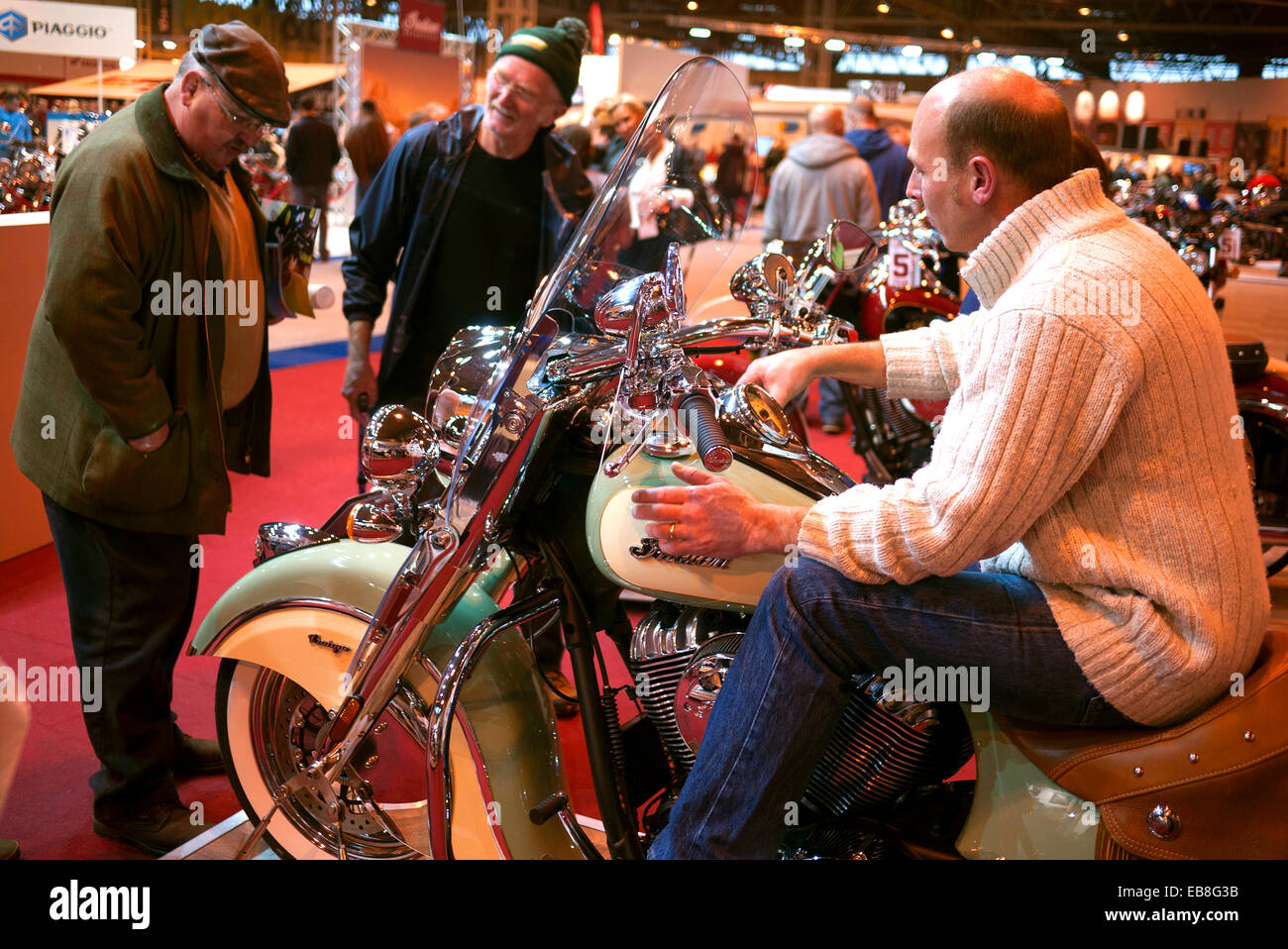 Visitors to the Motorcycle Live show at Birmingham's NEC, take a look at an Indian motorcycle. - Stock Image
