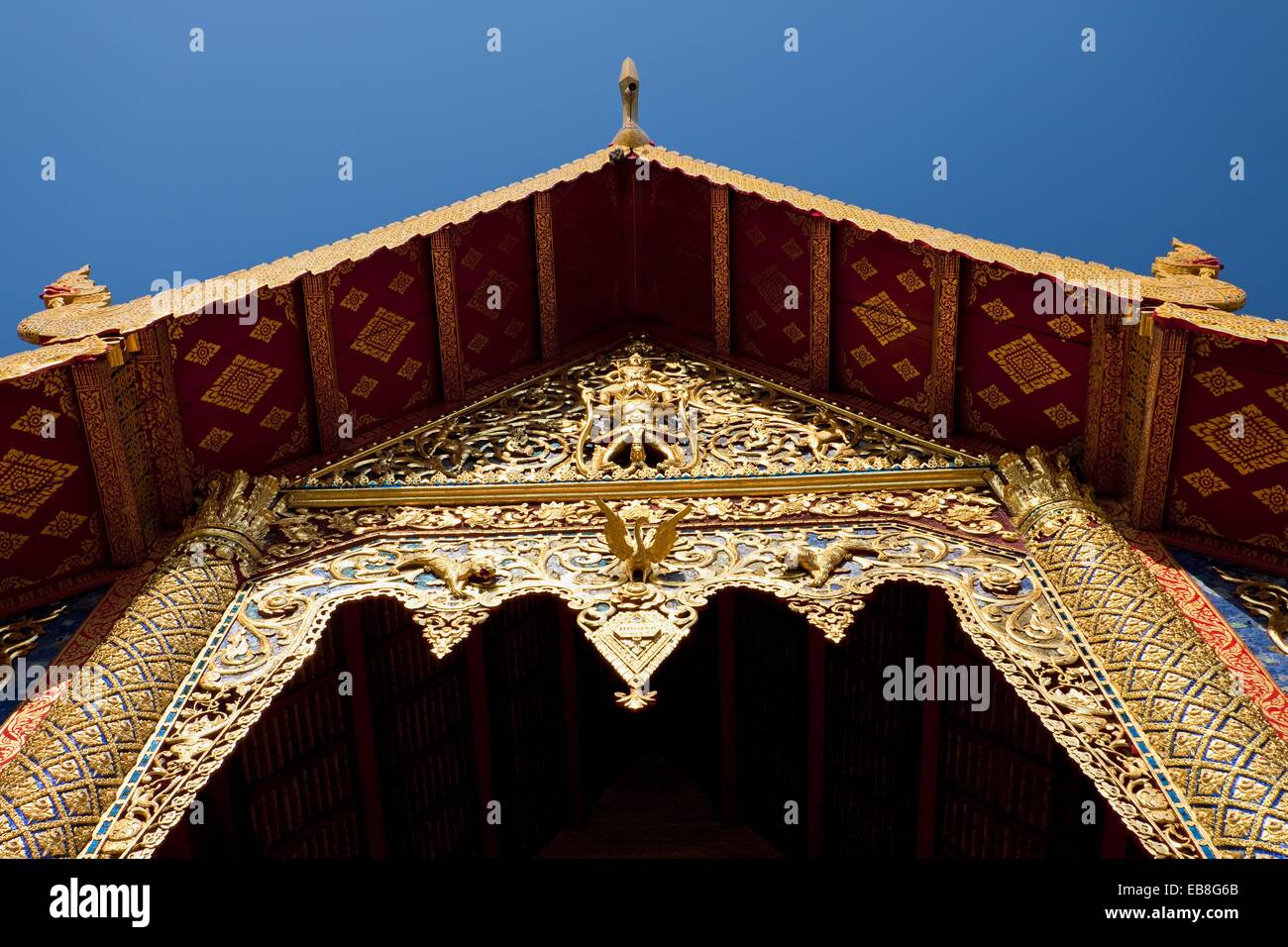 Carved woodwork above entrance to Wihaan or Ordination Hall, Wat Phra Singh, Chiang Mai, Thailand - Stock Image