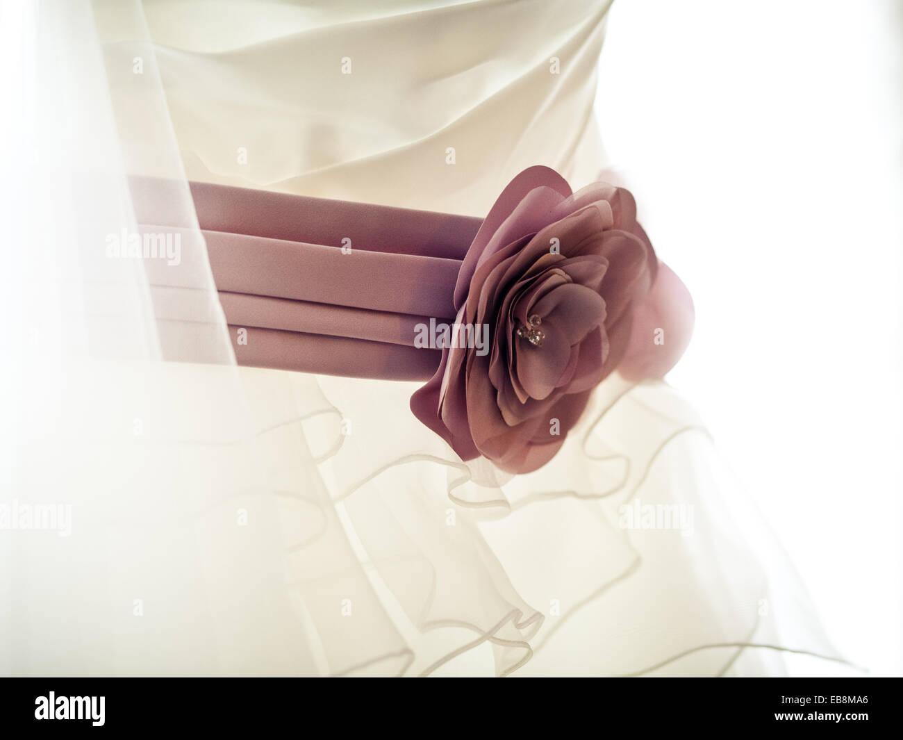 Pink silk flower band or belt on cream / white wedding dress, close up detail - Stock Image