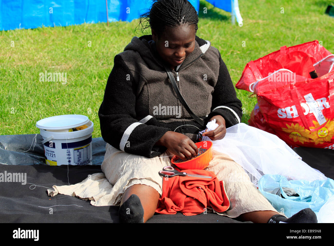 Local lady doing African beading to sell at the Kirstenbosch Craft Market  Cape Town, South Africa. - Stock Image