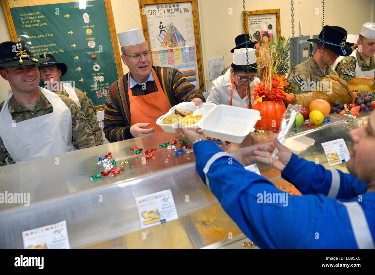 US Deputy Secretary of Defense Bob Work (center) serves sliced turkey to troops waiting in line for Thanksgiving - Stock Image