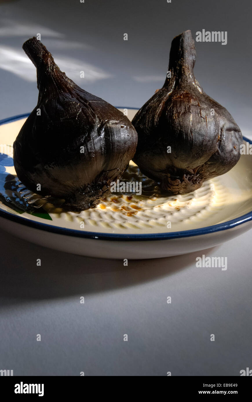 Black garlic bulbs whose unique coffee and chocolate flavor is a result of applying low heat over a period of several weeks Stock Photo