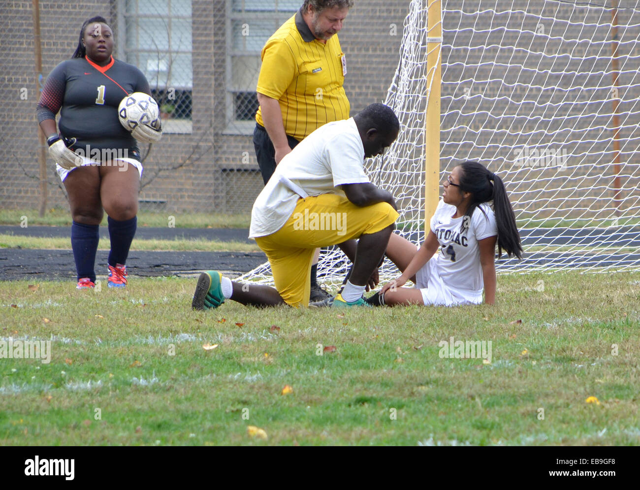 injured female soccer player is checked out by the coach and referee at a soccer game in Oxon Hills, Md - Stock Image