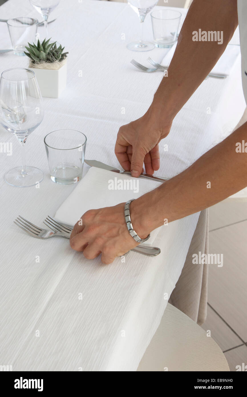 Close up of Waiter's Hands Arranging Cutlery on Restaurant Table Stock Photo