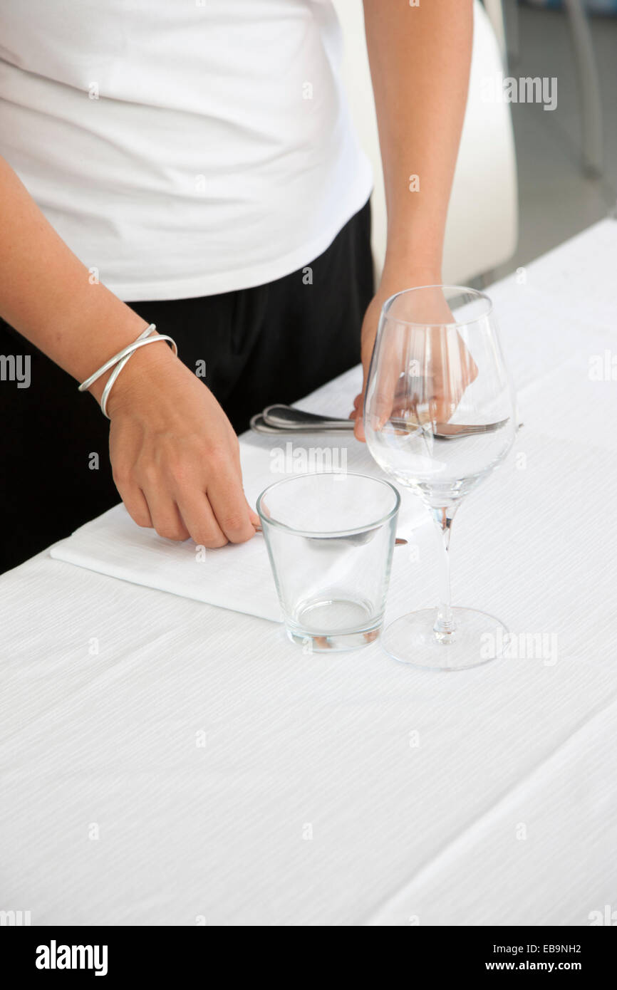 Close up of Waitress's Hands Arranging Cutlery on Restaurant Table Stock Photo