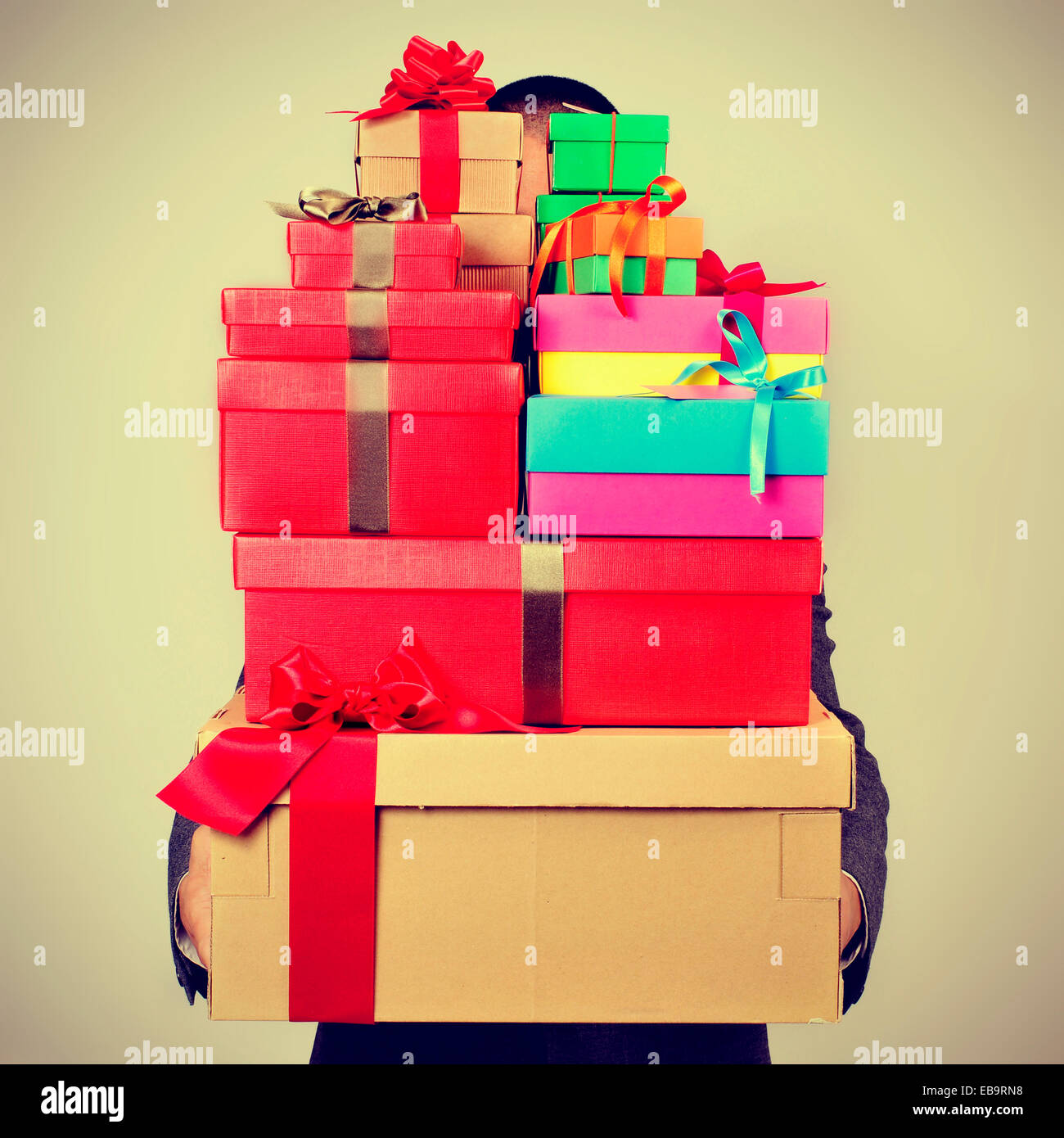 a young man in suit carrying a pile of gift boxes of different colors, with a filter effect - Stock Image