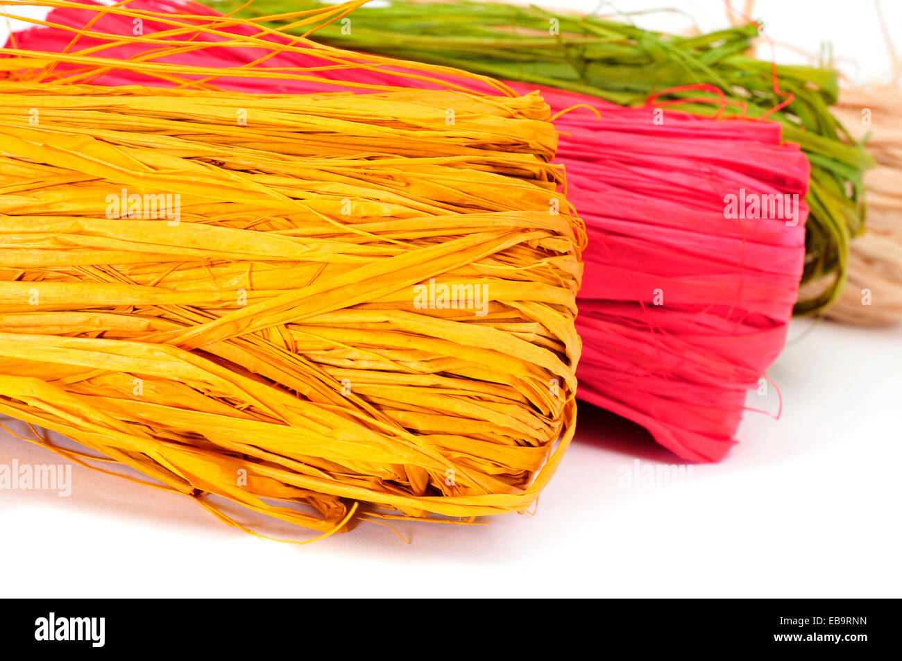 some skeins of natural raffia of different colors on a white background - Stock Image