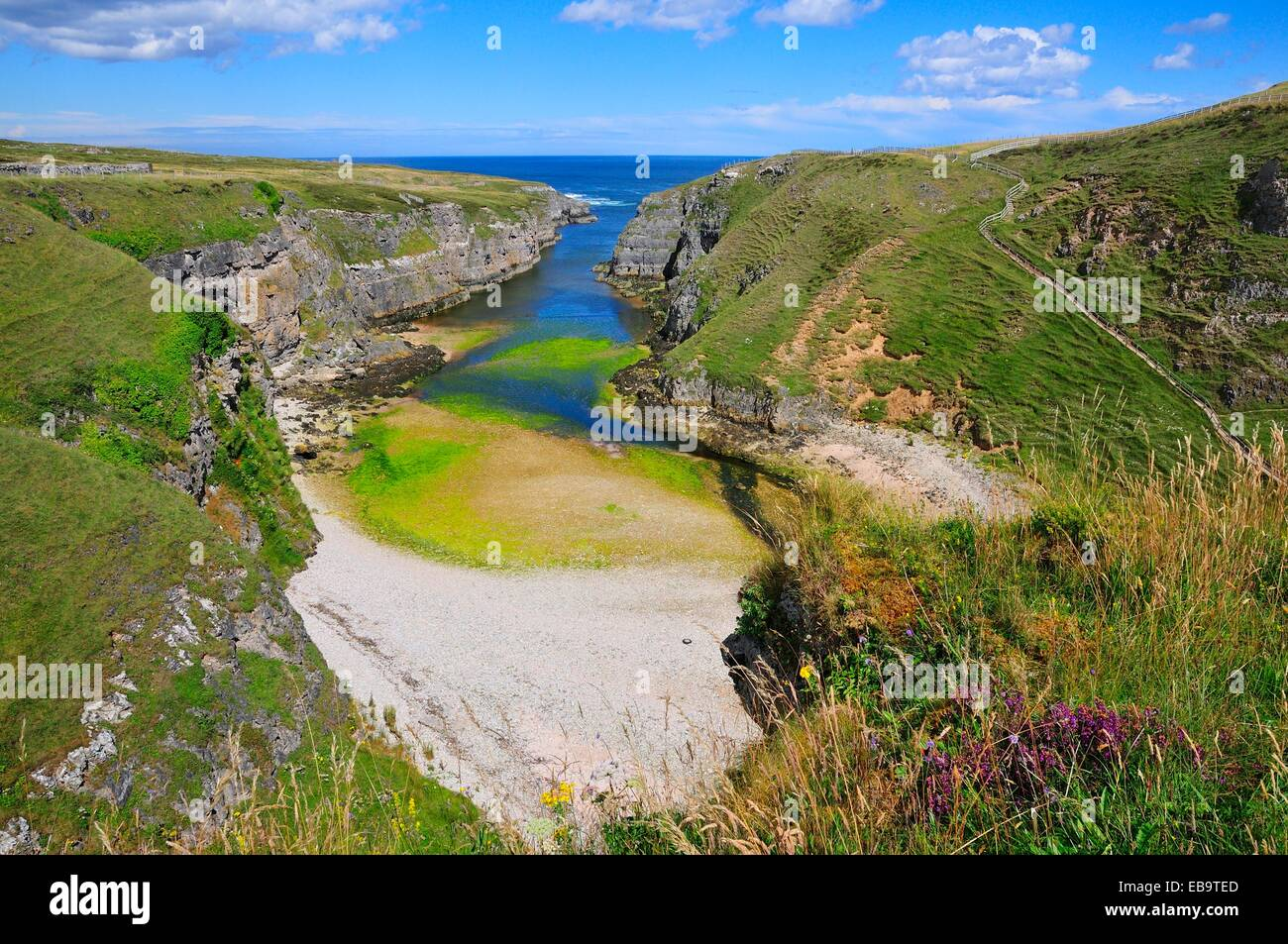 Sea inlet with a trail to a viewpoint at Smoo Cave, Durness, Caithness, Sutherland and Easter Ross, Scotland, United - Stock Image