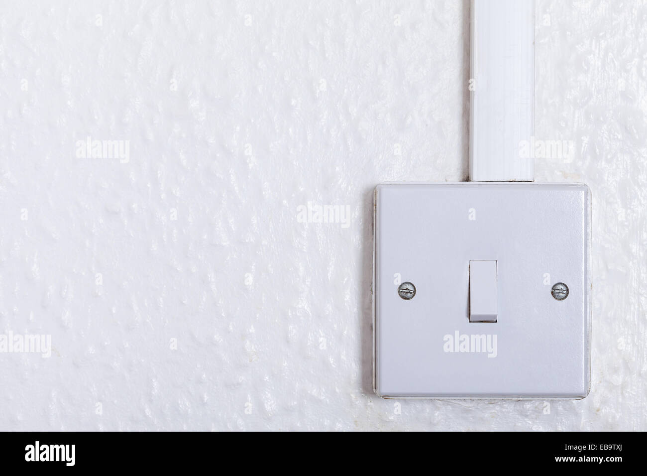 Light switch mounted on white wall with copy space. Old square box ...