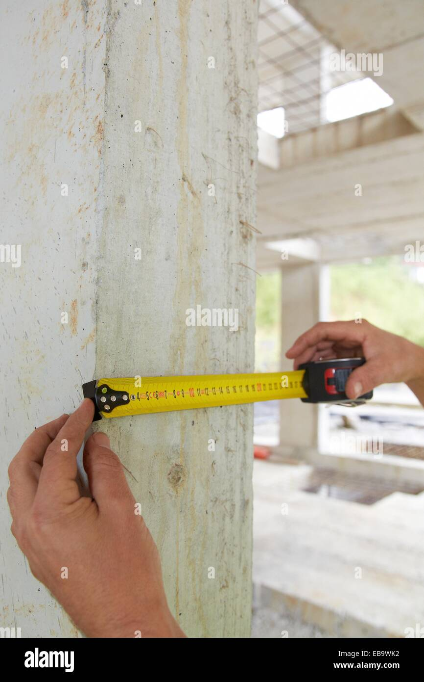 Taking measures in concrete beam, retractable tape, housing construction, Basque Country, Spain - Stock Image