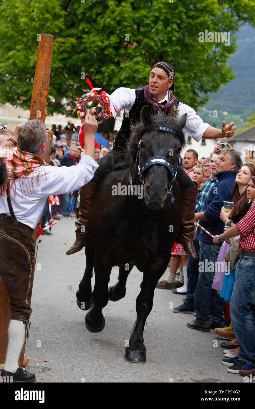 A man is handing a competitor a wreath of flowers, Kufenstechen, a traditional custom and festival, Feistritz an - Stock Image