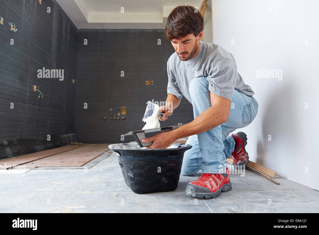 activity adhesive adult applying Basque Country beard bricklayer building built structure color image construction - Stock Image