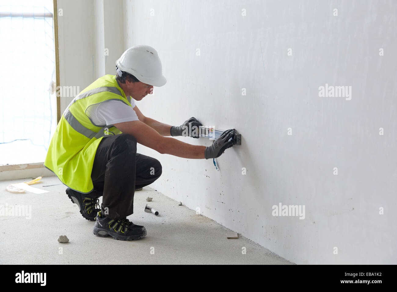 Construction worker with a level. Construction of residential building. Donostia. San Sebastian. Gipuzkoa. Basque - Stock Image