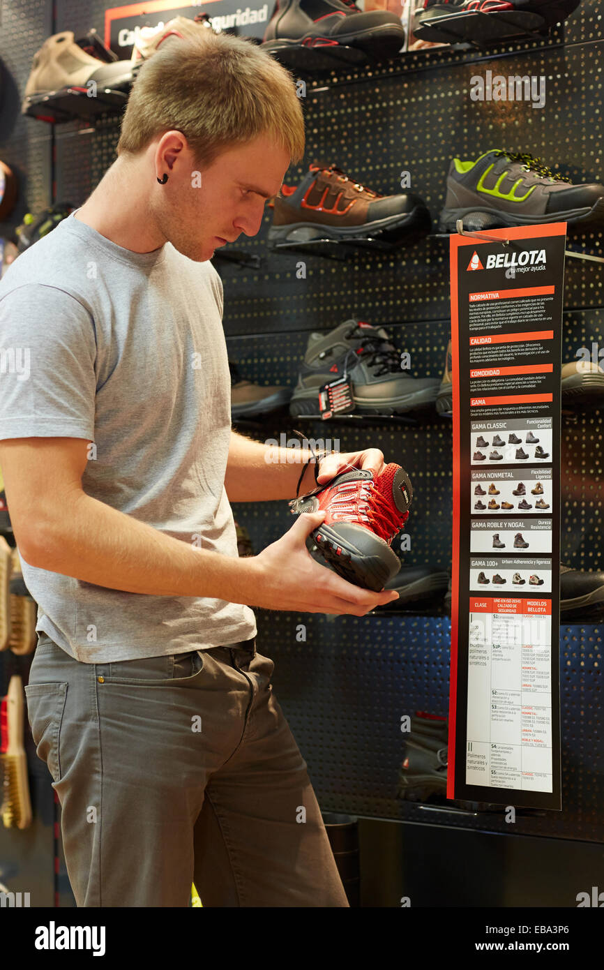 Buying protective boots. Hardware store. - Stock Image