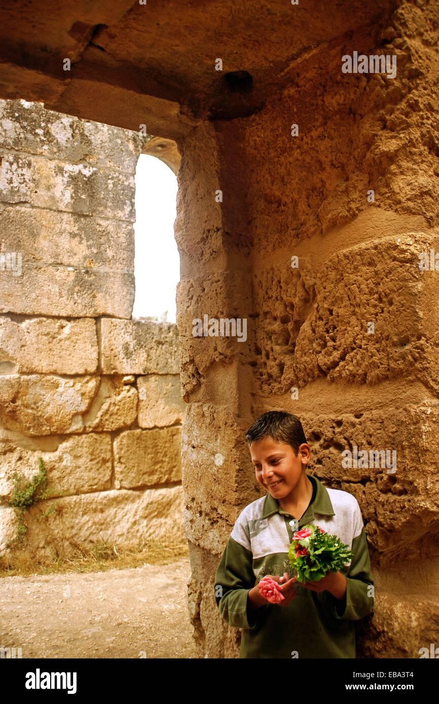 Boy at the baptistery of the Saint Simeon citadel, Qa´laat Samaan, Syria - Stock Image