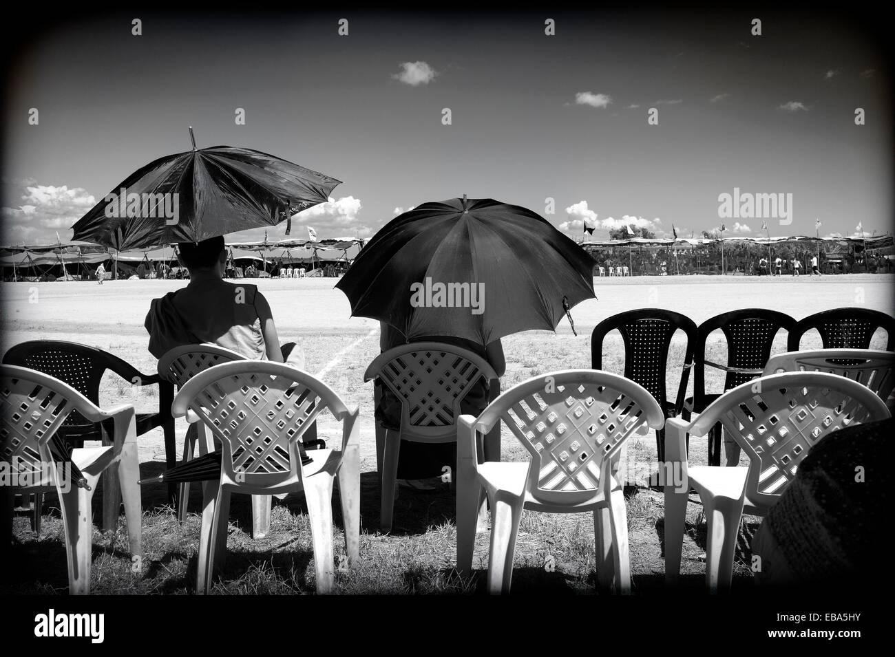 dos hombres de espaldas sentados, con paraguas, esperando en un campo de futbol, Campamento de refugiados Tibetano, - Stock Image