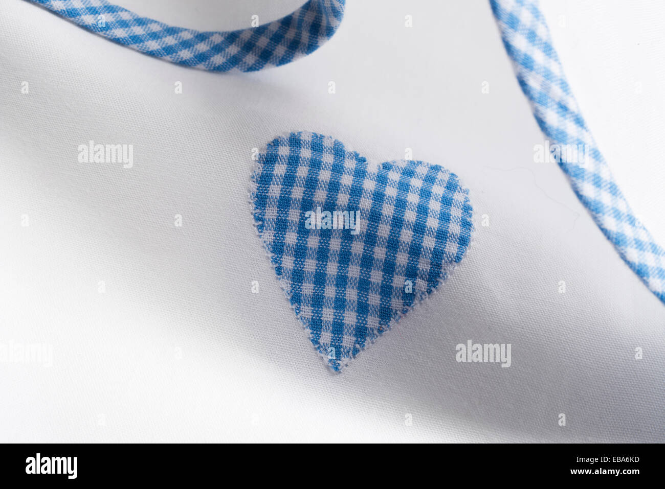 Gingham Appliqué hearts on white cotton sheet material. - Stock Image