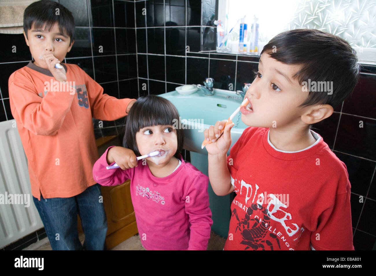 Brothers and sister brushing their teeth together, - Stock Image