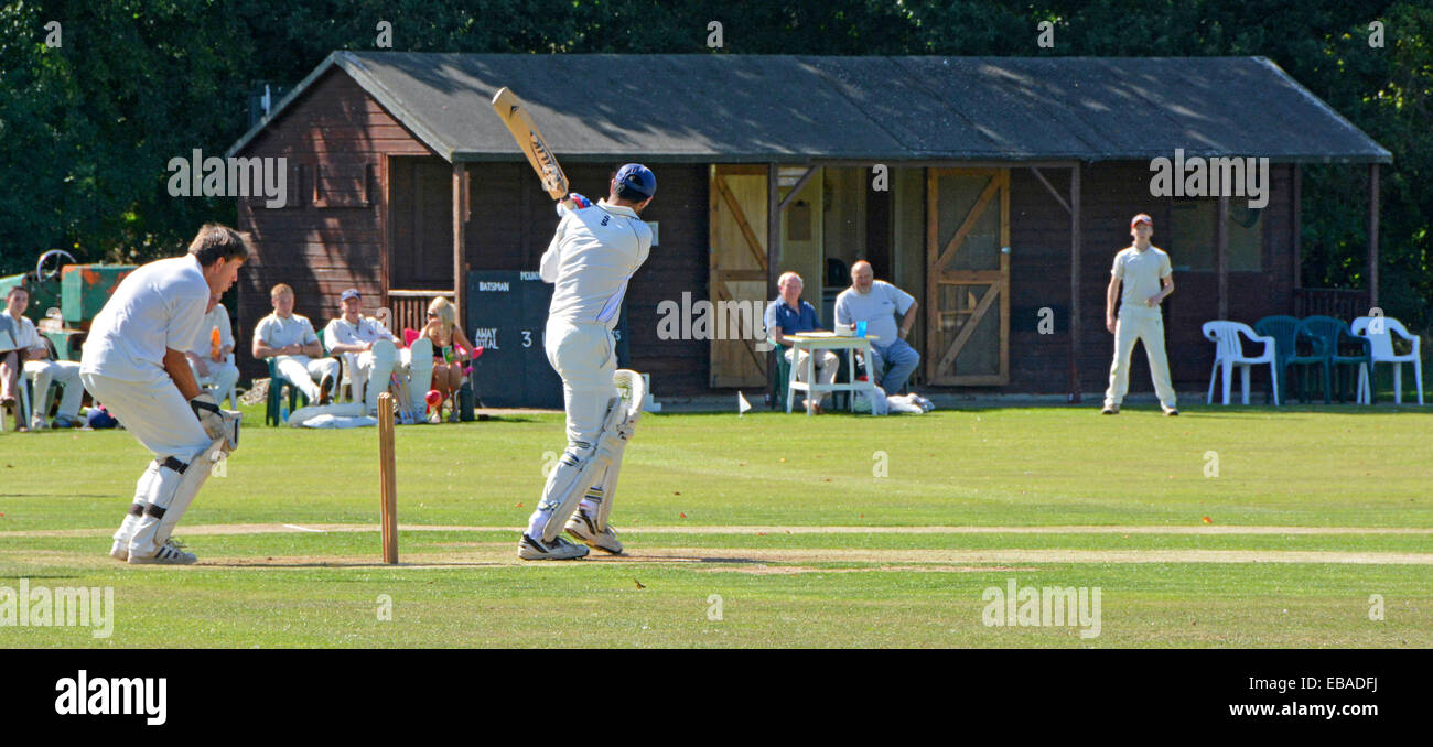 Close up of village green cricket match with batsman and wicket keeper - Stock Image